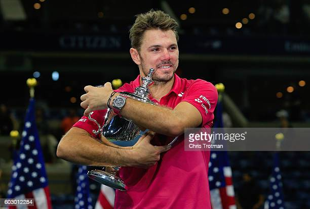 Stan Wawrinka of Switzerland celebrates with the trophy after winning 67 64 75 63 against Novak Djokovic of Serbia during their Men's Singles Final...