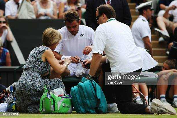 Stan Wawrinka of Switzerland receives treatment during his Gentlemen's Singles quarterfinal match against Roger Federer of Switzerland on day nine of...