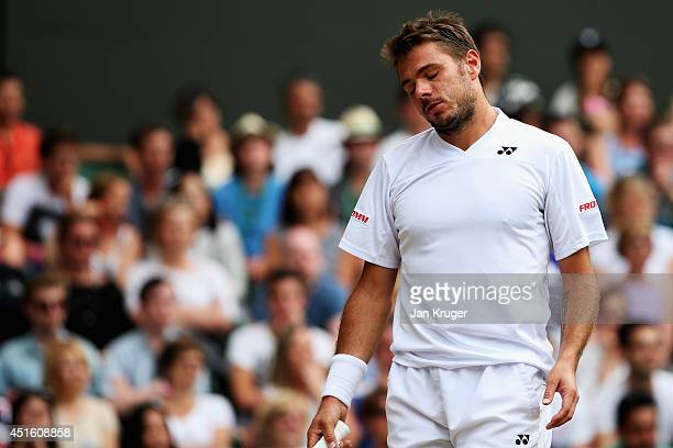 Stan Wawrinka of Switzerland stands dejected during his Gentlemen's Singles quarterfinal match against Roger Federer of Switzerland on day nine of...