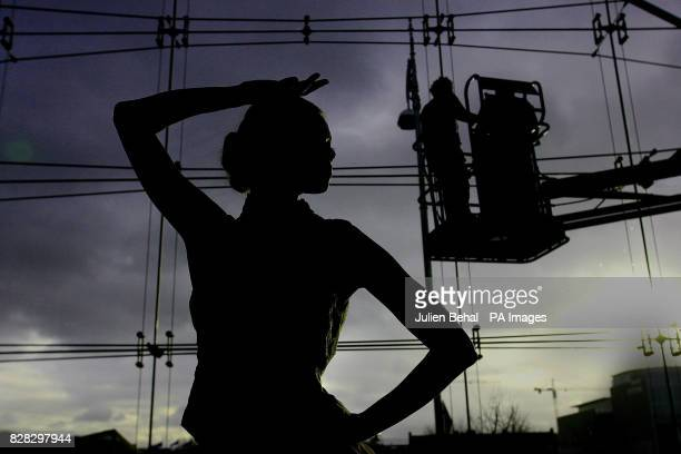 Stand Alone Pic Model Irma wearing a design by Joanne Hynes is captured in silhouette against a window with workmen on a cherry picker putting the...