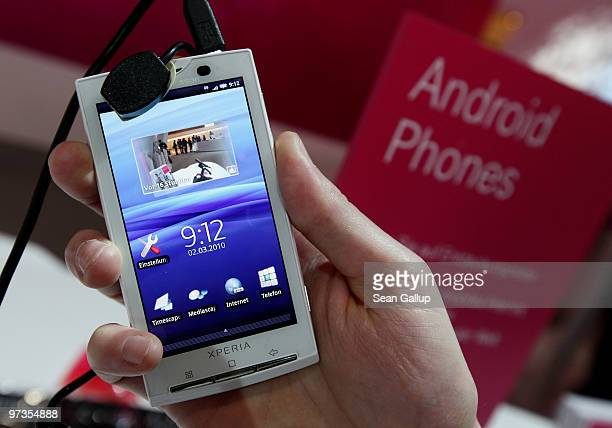 A stand host holds a Sony Ericsson XPERIA X10 mobile phone that uses the Android operating system at the Deutsche Telekom stand at the CeBIT...