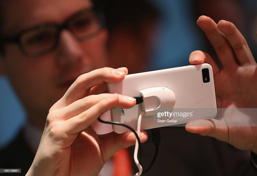 A stand host takes a picture with the Blackberry Z10 smartphone, which is the Germany version of the Blackberry 10, at the Vodafone stand at the 2013 CeBIT technology trade fair on March 5, 2013 in Hanover, Germany. CeBIT will be open March 5-9.