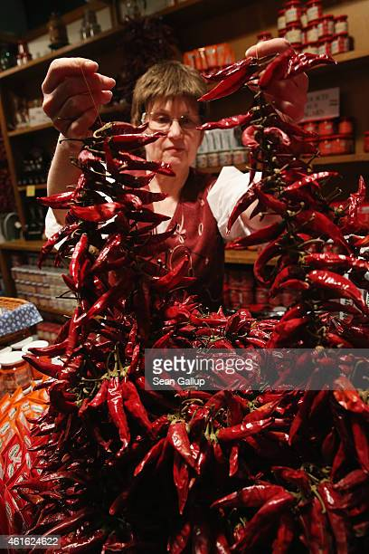 A stand hostess arranges bundled chili peppers that are used for making Hungarian paprika at the International Green Week agricultural trade fair on...