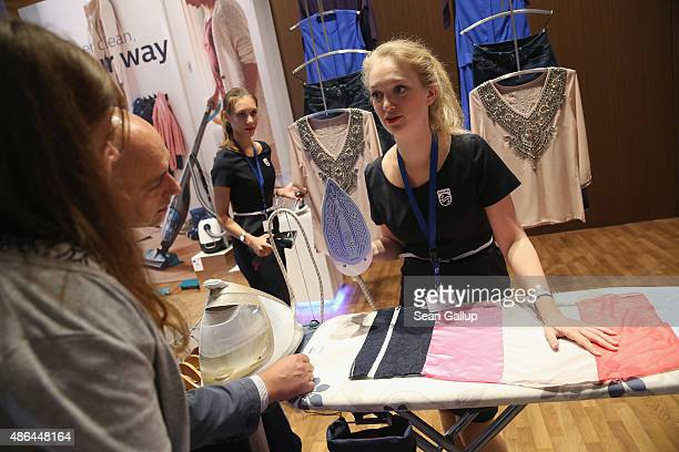 A stand hostess explains the merits of a new clothes iron at the Philips stand at the 2015 IFA consumer electronics and appliances trade fair on...