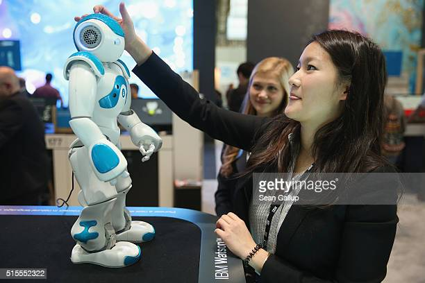 A stand hostess talks to a NAO Watson robot at the IBM stand at the 2016 CeBIT digital technology trade fair on the fair's opening day on March 14...