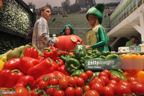 Stand hostesses dressed as garden vegetables stand next to fresh vegetables on display at the Netherlands hall at the 2011 Gruene Woche agricultural...