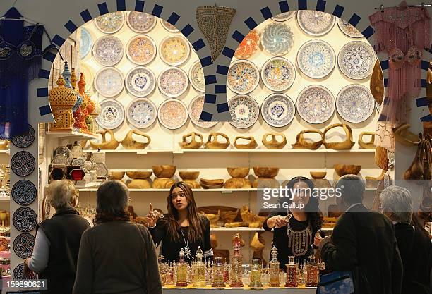 Stand hostesses sell alcoholfree perfume at a Tunisian stand at the 2013 Gruene Woche agricultural trade fair on January 18 2013 in Berlin Germany...