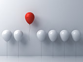 Stand out from the crowd and different concept , One red balloon flying away from other white balloons on white wall background with window reflections and shadows . 3D rendering.
