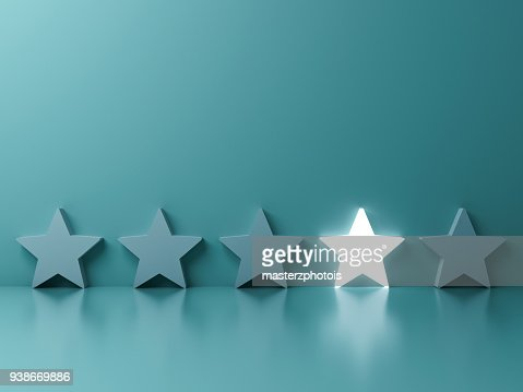 Stand out from the crowd and different creative idea concepts , One glowing star standing among other dim stars on green pastel color background with reflections and shadows : Stock Photo