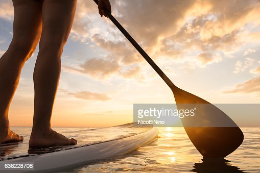 Stand up paddle boarding on quiet sea, legs close-up, sunset : Stock Photo
