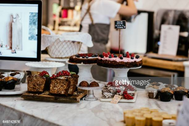 Stand with sweets in coffee shop, brownies, muffins, sweet bread