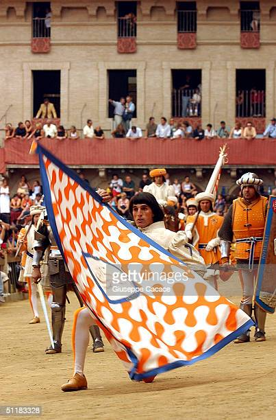 A standard bearer belonging to the Leocorno performs the flag waving display during the historical procession before the Palio horse race on August...