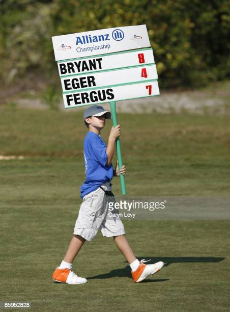 A standard bearer walks down the fairway during the second round of the Allianz Championship held at The Old Course at Broken Sound Club in Boca...