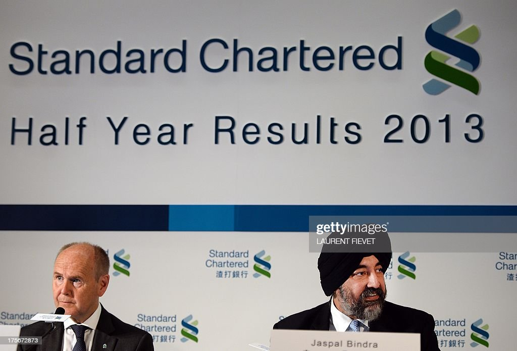 Standard Chartered group executive director and chief executive officer Asia Jaspal Bindra (R) speaks while chairman John Peace during a press conference prior to announcing the company's half year result in Hong Kong on August 6, 2013. Standard Chartered said its first-half net profit fell 24 percent in a turbulent global economy coupled with increased regulation. AFP PHOTO / Laurent FIEVET