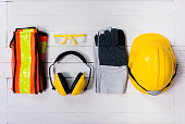 Standard construction safety equipment on white wooden background. top view, safety first concepts