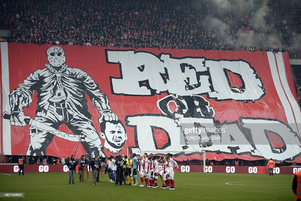 Standard de Liege fans display a banner featuring an illustration depicting the decapitation of Anderlecht midfielder <a gi-track='captionPersonalityLinkClicked' href=/galleries/search?phrase=Steven+Defour&family=editorial&specificpeople=5733692 ng-click='$event.stopPropagation()'>Steven Defour</a> before the Jupiler Pro League match between Standard de Liege and RSC Anderlecht, in Liege on January 25, 2015, on day 23 of the Belgian soccer championship. Fans of Belgian giants Standard Liege caused outrage when they unfurled a banner showing a mocked-up image of former captain <a gi-track='captionPersonalityLinkClicked' href=/galleries/search?phrase=Steven+Defour&family=editorial&specificpeople=5733692 ng-click='$event.stopPropagation()'>Steven Defour</a> being beheaded. The sick banner showed a masked man holding a blood-covered machete in his right hand and the severed head of Defour in the other. AFP PHOTO/BELGA / YORICK JANSENS - Belgium Out