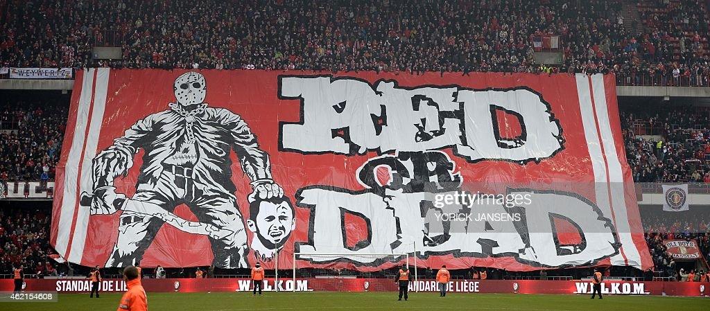 Standard de Liege fans display a banner featuring an illustration depicting the decapitation of Anderlecht midfielder Steven Defour before the...
