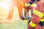 standby firefighter  hold hydrant nozzle and team background with flare and copy space