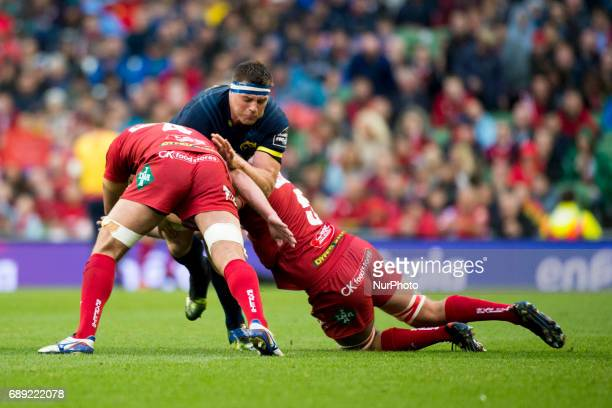 CJ Stander of Munster tackled by Lewis Rawlings and Tadhg Beirne of Scarlets during the Guinness PRO12 Final between Munster Rugby and Scarlets at...