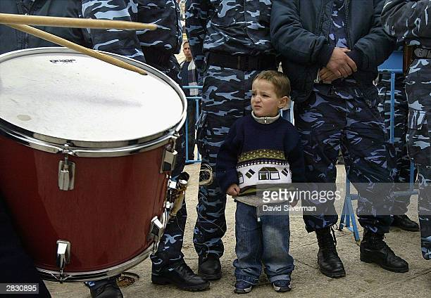 Standing at the feet of Palestinian police a young Palestinian boy watches Christian scouts march by during the annual Christmas Eve procession...