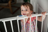Front view of a little girl standing on the other side of a baby saftey gate. The little girl is holding onto the top of the saftey gate and looking at the camera over the top.