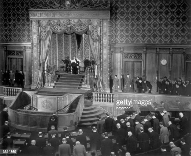 Standing before the gold and red Imperial Throne Emperor Hirohito of Japan prepares to read his script from a paper scroll to open the 89th session...
