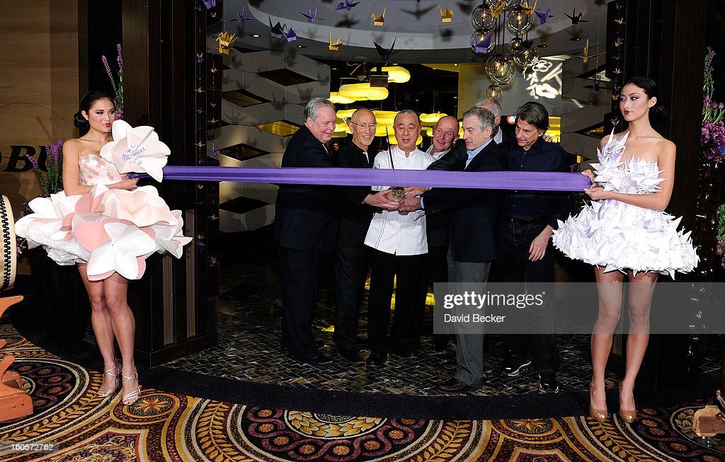 Standing between two models wearing orgami style dresses President of Caesars Entertainment Corp Western Division Tom Jenkin Meir Teper chef Nobu...