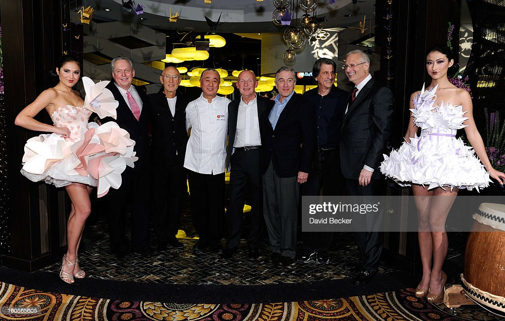 Standing between two models wearing origami style dresses (L-R) President of Caesars Entertainment Corp. Western Division Tom Jenkin, Meir Teper, chef Nobu Matsuhisa, CEO of Nobu Hospitality Trevor Horwell, actor Robert De Niro, Caesars Palace President Gary Selesner and designer David Rockwell appear appear during ribbon cutting ceremony at a preview for the Nobu Restaurant and Lounge Caesars Palace on February 2, 2013 in Las Vegas, Nevada. The Nobu Hotel Restaurant and Lounge Casears Palace is scheduled to open on February 4.
