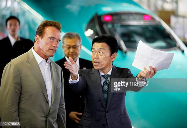 Standing by a bullet trains California Governor Arnold Schwarzenegger listens to Masaki Ogata vice president of East Japan Railway Co one of the...