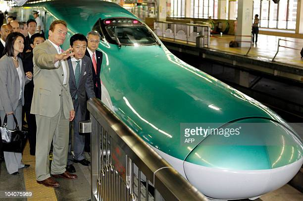 Standing by a bullet trains California Governor Arnold Schwarzenegger gestures as he listens to Masaki Ogata vice president of East Japan Railway Co...