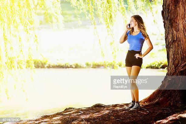 Standing by idyllic sunlit lake, pretty teenager talks on cellphone