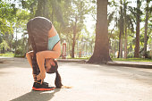 Sporty woman sportswoman doing a standing forward bend in the park