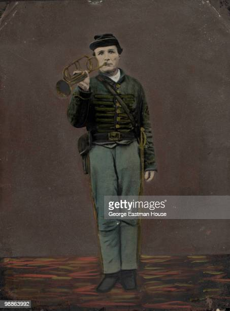 Standing full length portrait of an unidentified Civil War bugler ca1863 He holds the bugle to his lips and is wearing a sword on his side