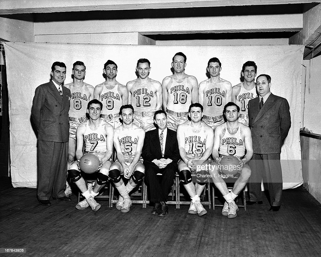 Standing (L-R) George Senesky #8,Ralph Kaplowitz #9, Howie Dallmar #12, Art Hillhouse #18, Joe Fulks #10, Matt Goukas #14, seated (L-R) Jerry Rullo #7,Angelo Musi #5, Petey Rosenberg #15, Jerry Fleishman #6 and head coach Ed Gottlieb pose for a portrait circa 1947 at the Philadelphia Civic Center in Philadelphia, Pennsylvania.