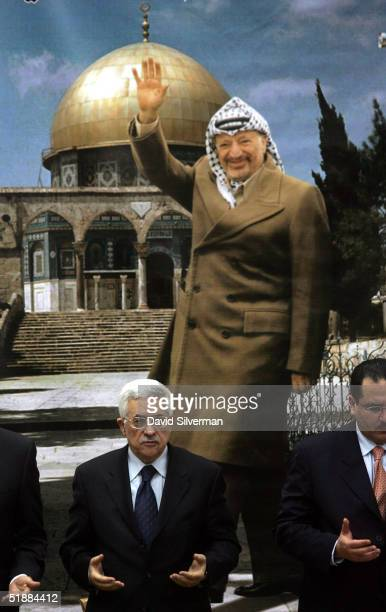 Standing in front of a poster of the late Palestinian leader Yasser Arafat and Jerusalem's Dome of the Rock Islamic shrine Palestinian interim leader...