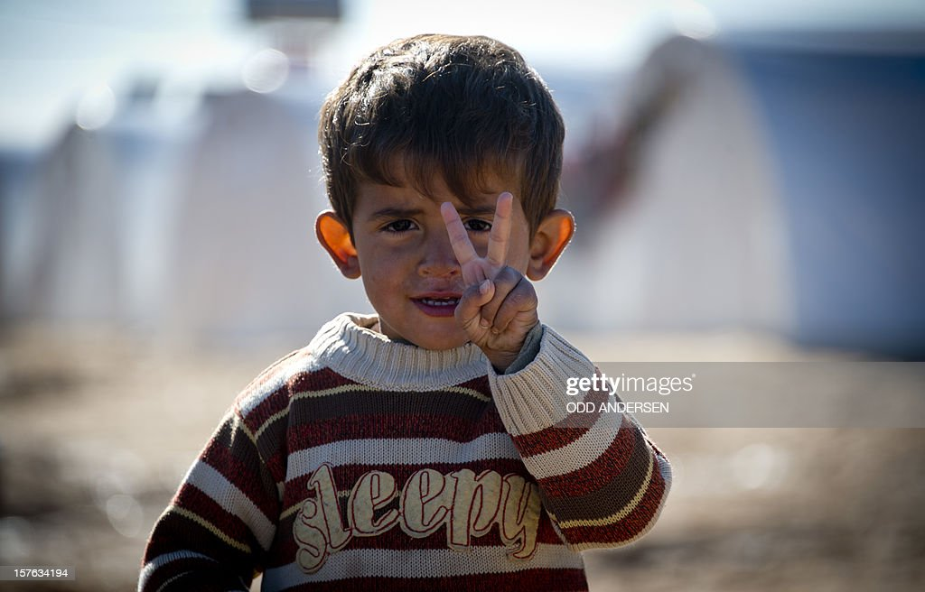 Standing in front of a row of plastic tents a young boy flashes the V-sign in a refugee camp on the border between Syria and Turkey near the northern city of Azaz on December 5, 2012. The internally displaced faced further misery as heavy rain was followed by a drop in temperatures. The United Nations estimated late October that more than 2.5 million people have been affected by the fighting in Syria. There are more than 348,000 Syrian refugees registered in neighbouring countries, but many more are unregistered. AFP PHOTO / ODD ANDERSEN