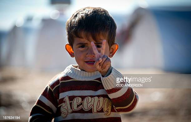 Standing in front of a row of plastic tents a young boy flashes the Vsign in a refugee camp on the border between Syria and Turkey near the northern...