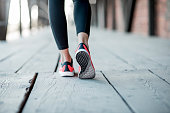 Sports woman in running shoes standing back on the wooden floor, close-up view focused on the sneakers
