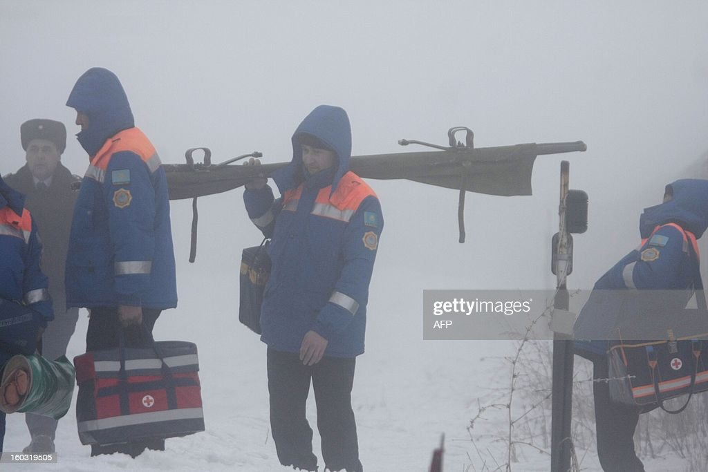 Standing in thick fog paramedics crowd near the site of the plane crash some 30 km outside the Kazakhstan's commercial capital of Almaty, on January 29, 2013. A passenger plane crashed today in thick fog near Almaty killing all 22 people on board, an emergencies services official said. AFP PHOTO / ANATOLY USTINENKO