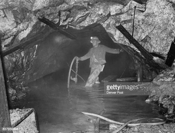 Standing kneedeep in water a miner holds a water suction pump inside a small tunnel deep beneath the Continental Divide The small tunnel and a...
