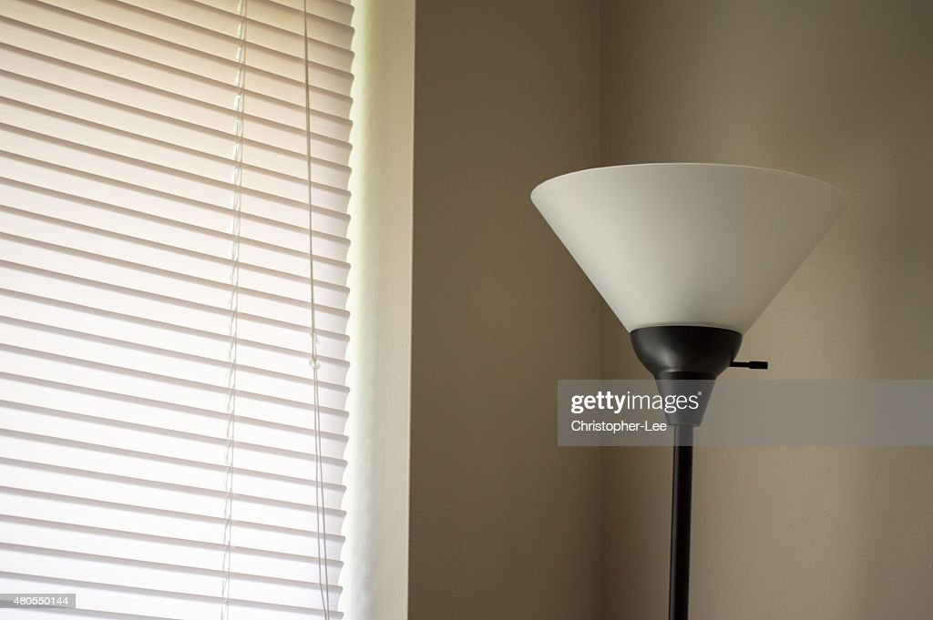 Standing lamp next to a window : Stock Photo