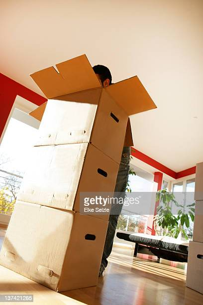 Standing man searching boxes in empty apartment