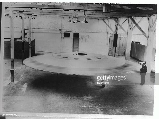 Standing next to this 25foot wide French flying saucer aircraft is its designer Rene Couzinet who claims it is capable of attaining speeds above 1000...