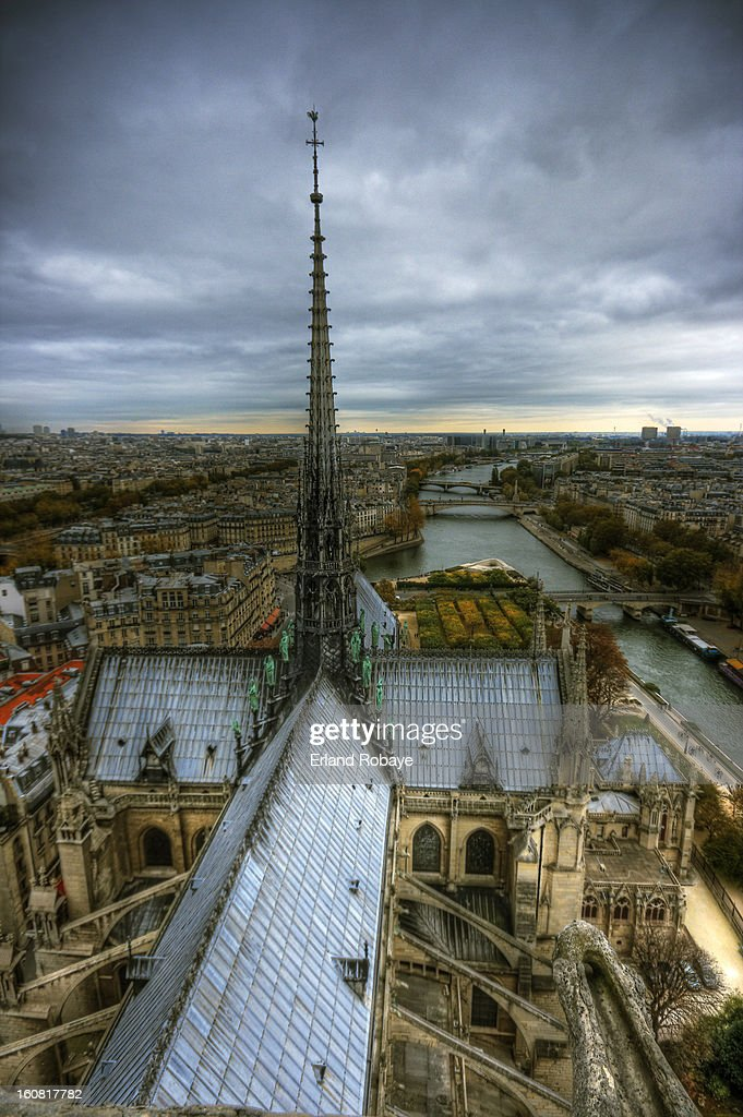 CONTENT] Standing on the roof of towers of the famous Notre Dame Cathedral and looking over the Seine river with the cross shaped roof of the cathedral in view.