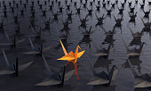 Standing out from the crowd concept with an orange colored paper crane between the black ones on the water. ( 3d render )