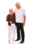 Standing portrait of a tall senior man with his short wife.  Isolated on white.