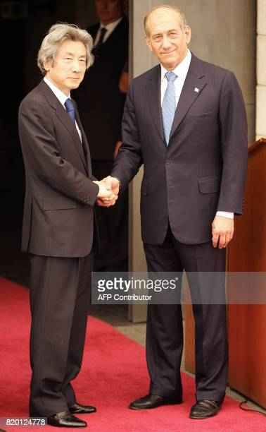Standing under a canopy Japanese Prime Minister Junichiro Koizumi shakes hands with Israeli Prime Minister Ehud Olmert at his offices in Jerusalem 12...