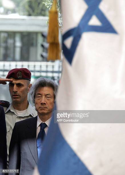 Standing under a canopy Japanese Prime Minister Junichiro Koizumi stands to attention during the honor guard ceremony along with Israeli Prime...