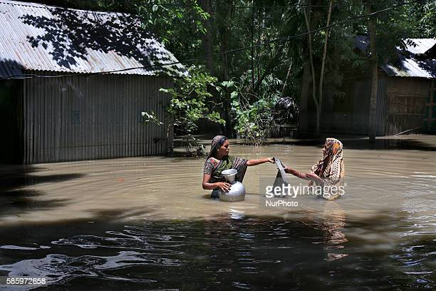 stands highdeep in flood water as he collects water from a tube wale