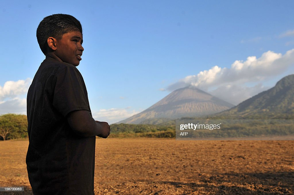 A stands in a field in Grecia 4, Chinandega, 150 km from Managua, with the San Cristobal volcano in the background on December 26, 2012. The San Cristobal volcano began spewing smoke and ashes Tuesday afternoon. AFP PHOTO / Hector RETAMAL